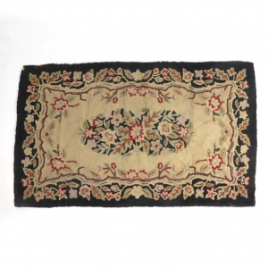SOLD: Vintage hooked rug with floral motif on black and natural ground